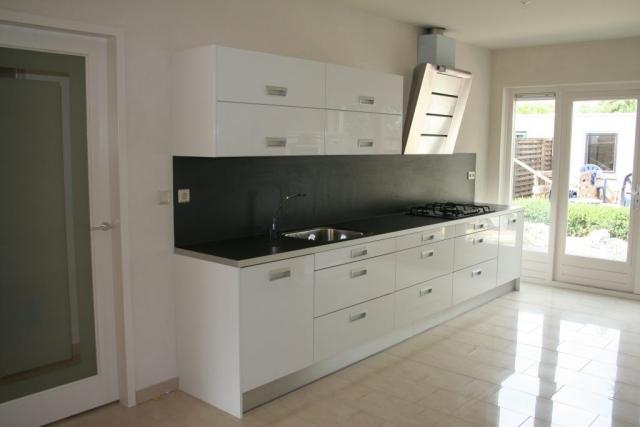 Hoogglans witte keuken met strakke afzuigkap
